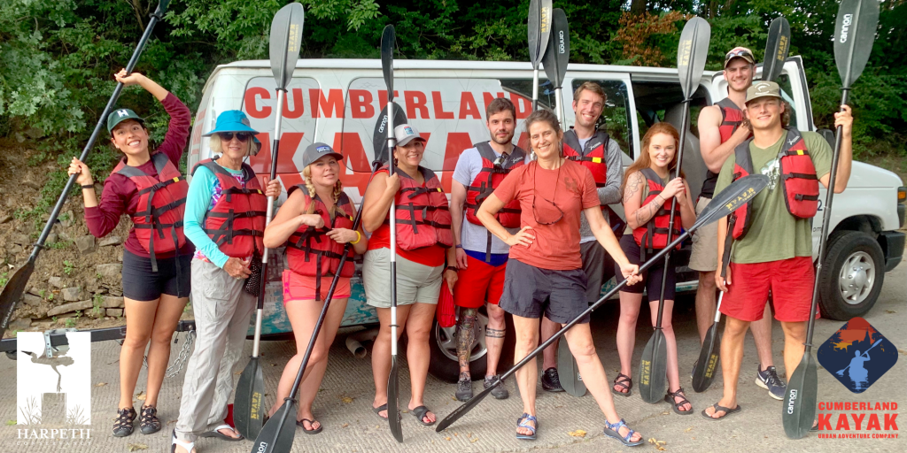 Individuals standing together with oars and in lifejackets